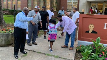 Fathers lined the walkway of this school to cheerfully welcome students back