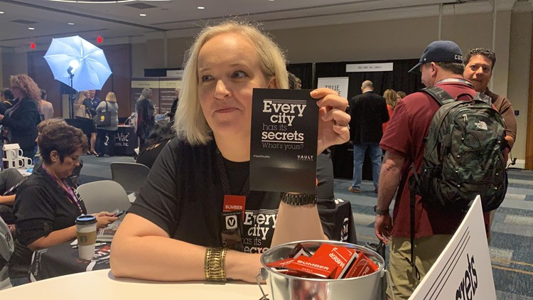 """Jessica Noll, co-host of the upcoming True Crime Chronicles podcast, poses with one of her """"tip cards,"""" which she'll use to find story ideas for future podcast episodes"""