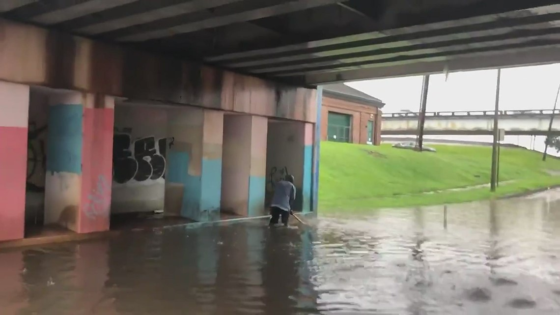City worker clearing drains under Marconi Drive during Flash Flood Warning