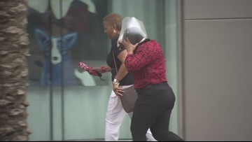 Pedestrians fight the wind on Canal Street ahead of Tropical Storm Barry